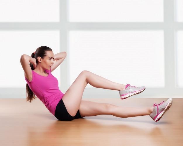 Een vrouw uit te oefenen crunches fitness workout armen achter het hoofd Premium Foto