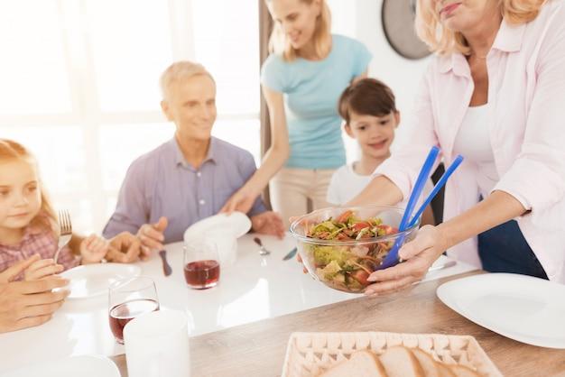 Een vrouw van middelbare leeftijd serveert een salade voor haar gezin. Premium Foto