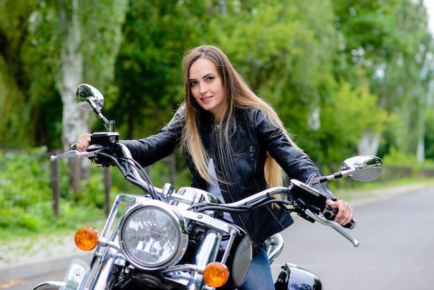 Een vrouw zit op een motorfiets en lacht. Premium Foto