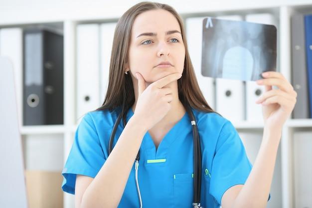 Een vrouwelijke arts met een serieuze blik onderzoekt een röntgenfoto Premium Foto