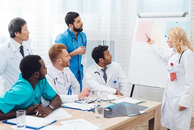 Een vrouwelijke arts toont ander artsendocument op een witte raad. Premium Foto