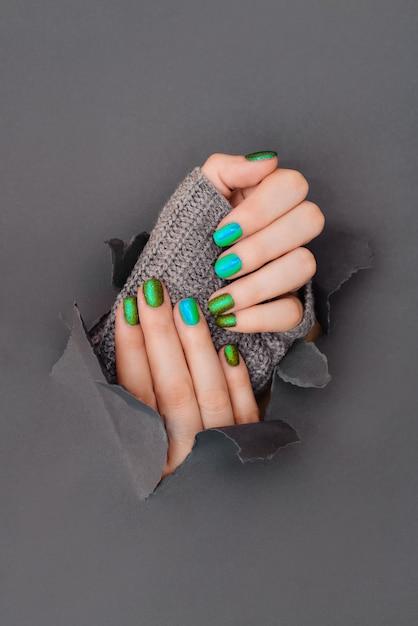 Een vrouwelijke hand met lente groene mint gekleurde nagellak bij het houden van een takje tegen een groene achtergrond Premium Foto