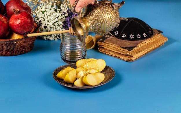Een vrouwelijke hand neemt honing met honing voor de appelschijf en granaatappelvakantie van rosh ha shana Premium Foto