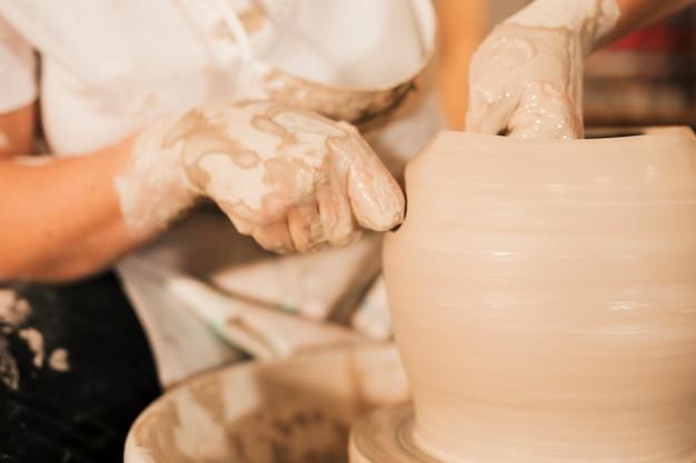 Een vrouwelijke pottenbakker werkt aan het maken van een aarden pot aan het pottenbakkerswiel Gratis Foto