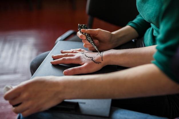 Een vrouwelijke toepassing van mehndi tatoeage over de hand van de vrouw Gratis Foto