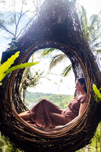 Een vrouwelijke toerist zit op een groot vogelnest op een boom bij ba Premium Foto
