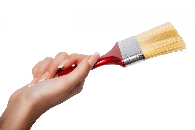 Een vrouwelijke (vrouwen) hand houdt een rode borstel geïsoleerd wit, bovenaanzicht in de studio. Premium Foto