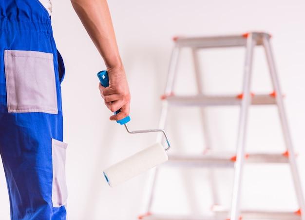 Een werkende man houdt een gereedschap in zijn hand en is klaar om te werken. Premium Foto