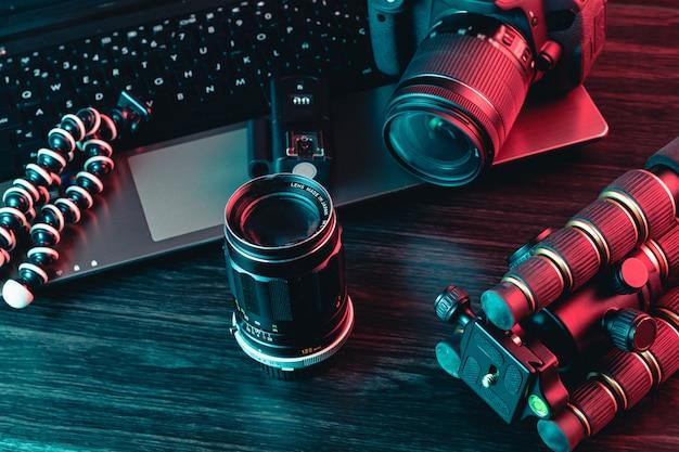 Een werkruimte met laptop, moderne camera, lens, statief en een pen Premium Foto