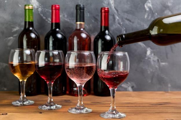 Een wijnfles vullend wijnglas Gratis Foto