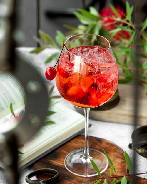 Een wijnglas met kersencocktail gegarneerd met kersen Gratis Foto
