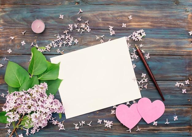 Een wit papier, lila, paarse kaars, inkt pen en twee roze harten op vintage houten achtergrond Premium Foto