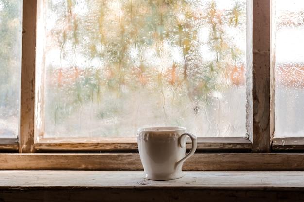 Een witte kop en oude boeken over een van een rustiek houten nat raam Premium Foto