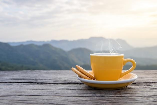 Een witte kop warme espresso koffiemokken geplaatst met koekjes op een houten vloer met ochtendmist en bergen met zonlicht achtergrond, koffie ochtend Premium Foto