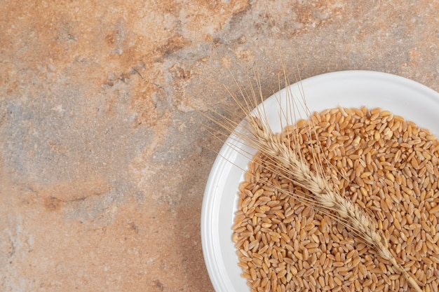 Een witte plaat van granen en tarwe op marmeren achtergrond. hoge kwaliteit foto Gratis Foto