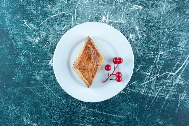Een witte plaat van heerlijk zoet gebak op een blauwe achtergrond. hoge kwaliteit foto Gratis Foto