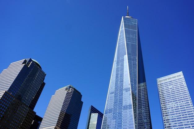 Eén world trade center in de stad vs van new york. uitzicht vanaf het 9.11 gedenkteken op een zonnige dag. Premium Foto