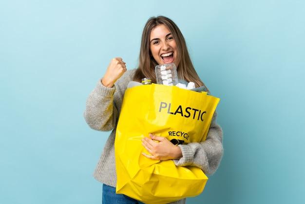 Een zak vol plastic flessen vasthouden om te recyclen op geïsoleerd blauw om een overwinning te vieren Premium Foto