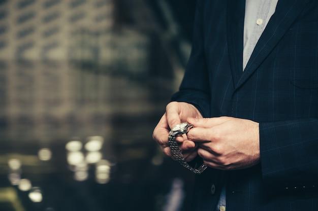 Een zakenman in een pak maakt tijd vrij in een polshorloge Premium Foto