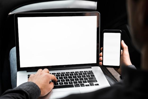 Een zakenman met behulp van laptop en mobiele telefoon met een leeg wit scherm Gratis Foto