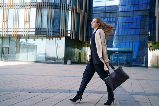 Een zakenvrouw in een jas en pak, met een tas in haar hand, loopt overdag in de buurt van het zakencentrum. Gratis Foto