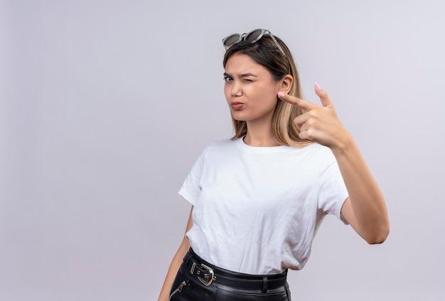 Een zelfverzekerde jonge vrouw in een wit t-shirt met een zonnebril op haar hoofd die met wijsvinger naar iets richt terwijl ze op een witte muur kijkt Gratis Foto