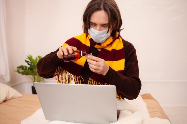 Een zieke man zit achter een laptop met een masker en een sjaal. coronavirus, covid, thuisquarantaine. de mens schenkt zichzelf medicijnen in, behandelt griep, verkoudheid Premium Foto