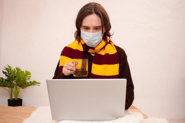 Een zieke man zit achter een laptop met een masker en een sjaal. coronavirus, covid, thuisquarantaine. een man drinkt thee van een verkoudheid. Premium Foto
