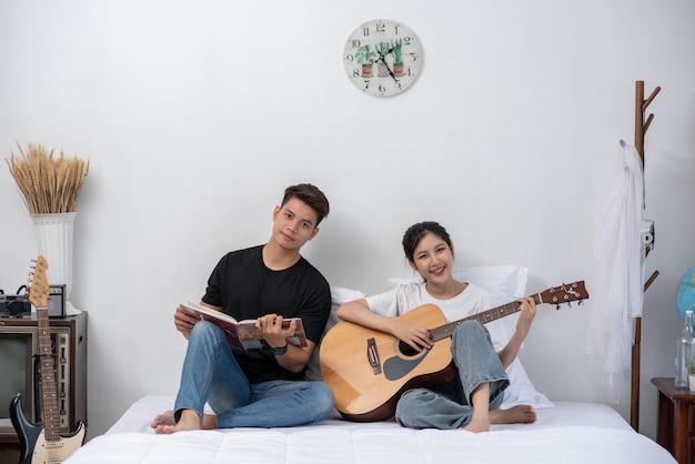 Een zittende vrouw speelt gitaar en een man die een boek vasthoudt en zingt. Gratis Foto
