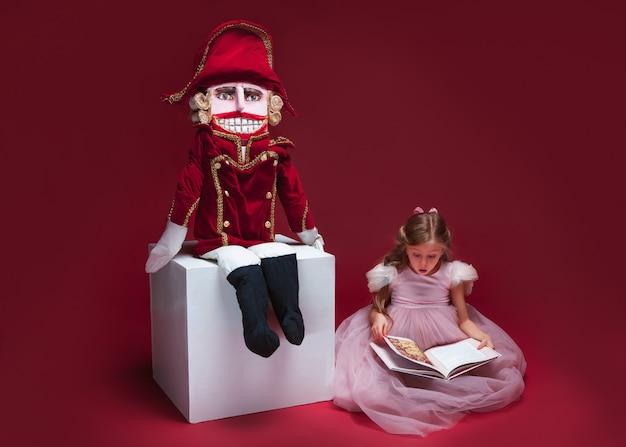 Een zitting van de schoonheidsballerina dichtbij notekraker en lezingsboek bij rode studio Gratis Foto