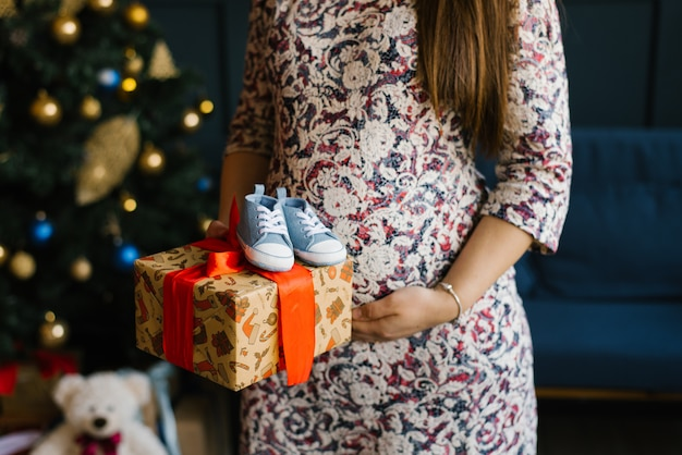 Een zwangere vrouw houdt een geschenkdoos met een rood lint en baby sneakers voor de baby in de buurt van haar buik tegen de achtergrond van een kerstboom Premium Foto