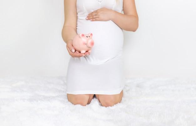 Een zwangere vrouw houdt een spaarvarken. Premium Foto