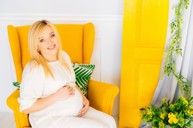 Een zwangere vrouw houdt haar armen op haar buik zittend in een zachte fauteuil Premium Foto