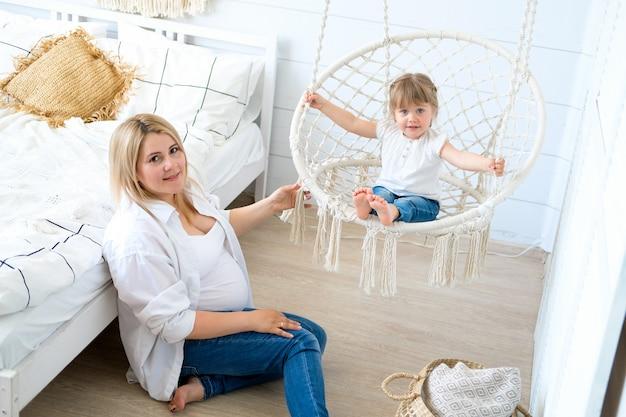 Een zwangere vrouw met haar dochtertje. baby die in een hangende stoel slingert, mamma die op de vloer zit. Premium Foto
