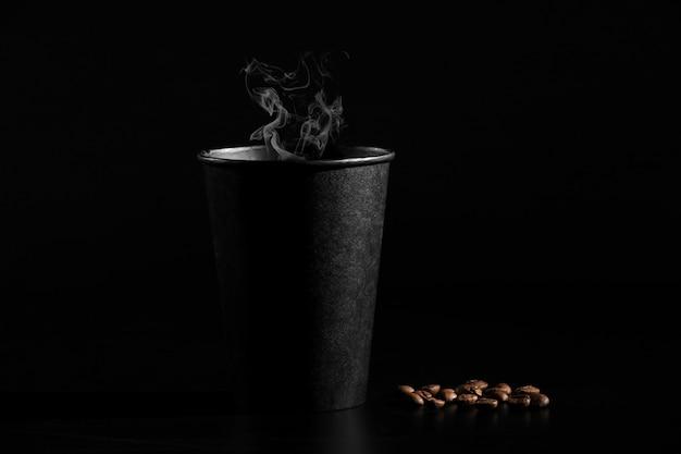 Een zwart glas hete koffie met verspreide koffiebonen op een zwarte achtergrond. detailopname Premium Foto