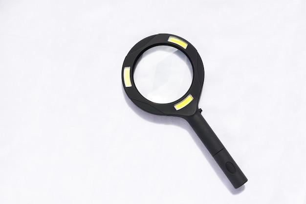 Een zwart vergrootglas met licht dat op witte achtergrond wordt geïsoleerd. Premium Foto