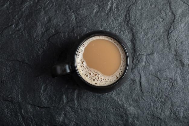 Een zwarte kop koffie op zwart. Gratis Foto