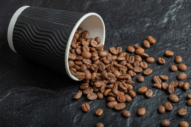 Een zwarte kop vol koffiebonen op een houten bord. Gratis Foto