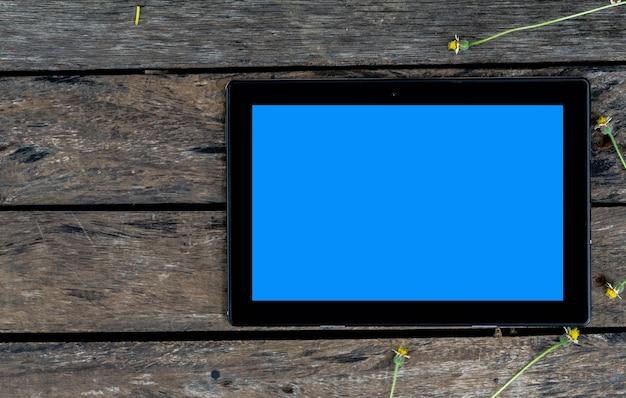 Een zwarte tabletcomputer met blauw scherm op oude houten tafel