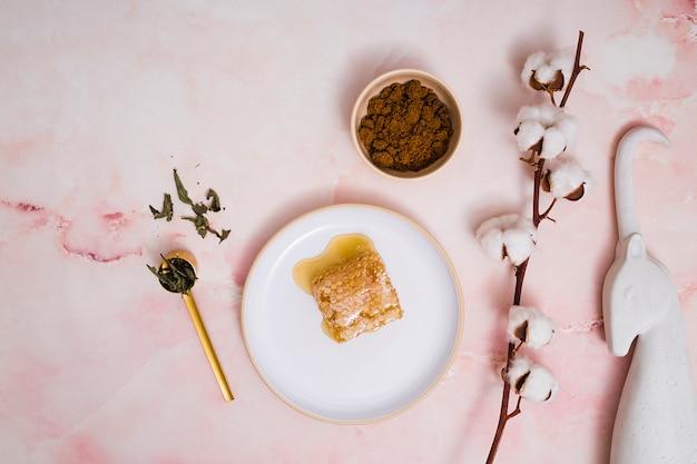 Eenhoorn standbeeld; koffiedik; verlaat; katoenen knoptakje met honingraat op keramiek tegen roze geweven achtergrond Gratis Foto