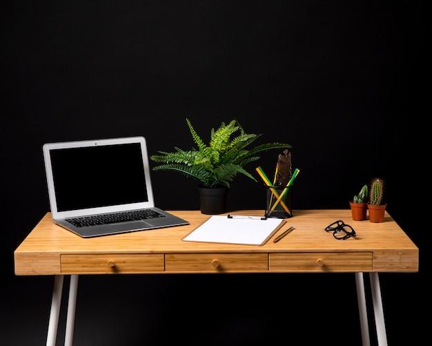 Eenvoudig houten bureau met klembord en laptop Gratis Foto