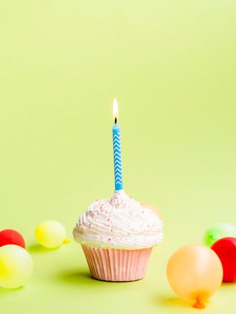Eenvoudige verjaardagsmuffin met kaars en ballons Gratis Foto