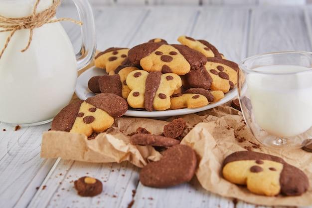 Eenvoudige zelfgemaakte zandkoekjes in de vorm van honden en vlinders met een glas melk Premium Foto