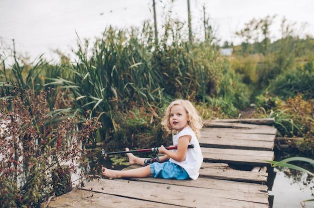Eenzaam klein kind vissen van houten dok op het meer Premium Foto