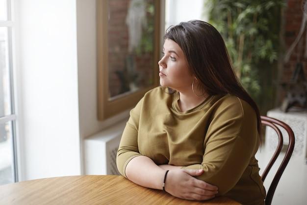 Eenzaamheid concept. jonge brunette plus size vrouw met zwart haar, zittend aan een cafétafel, zich eenzaam voelen, tijd alleen doorbrengen, wachten op haar lunch, door raam kijken met droevige peinzende uitdrukking Gratis Foto