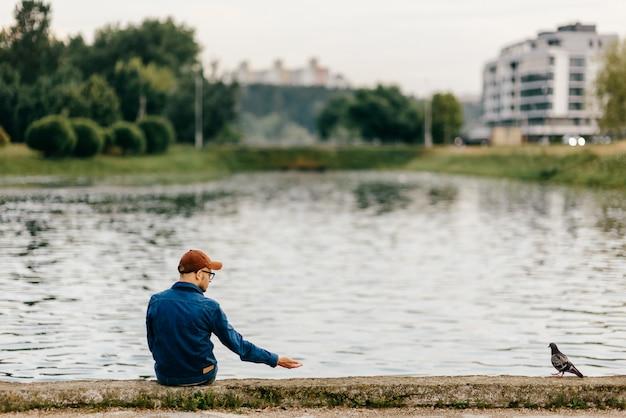 Eenzame onherkenbare volwassen man zittend op de rand van de dijk in de voorkant van het meer en roepen duif op zoek naar hem Premium Foto