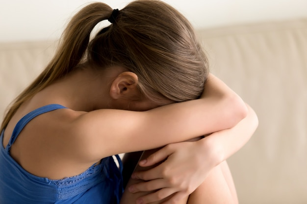 Eenzame vrouw knuffelen knieën en huilen Gratis Foto