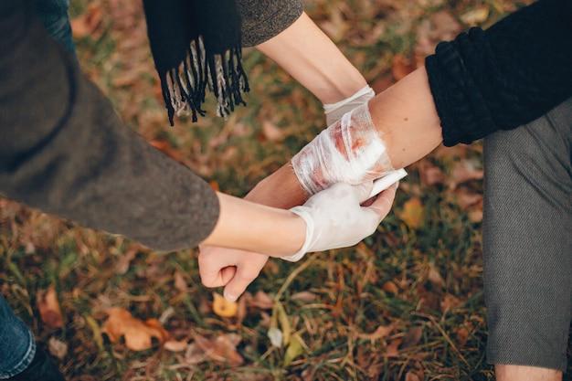 Eerste hulp verlenen in het park. man verbonden gewonde arm. guy helpt een vriend. Gratis Foto