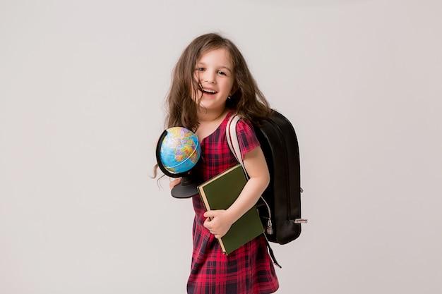 Eersteklasser met boeken en een wereldbol lachend Premium Foto
