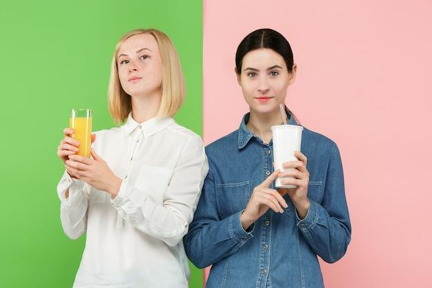 Eetpatroon. dieet concept. gezond eten. mooie jonge vrouwen die kiezen tussen sinaasappelsap en een onheldere, koolzuurhoudende zoete drank Gratis Foto
